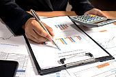 Businessmen are reviewing reports, financial documents for financial data analysis, work ideas and market data.