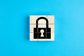 Lock icon on wooden cubes on blue background