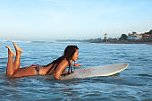 Surfing Girl In Bikini On White Surfboard In Ocean. Tanned Brunette Swimming In Sea. Water Sport For Active Lifestyle.