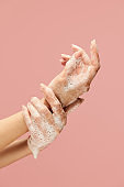 Washing Hands. Female Arms Covered With Soap Foam Against Pink Background. Using Antibacterial Products And Personal Hygiene For Infection Prevention.
