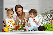 Woman With Children Cooking Healthy Food In Kitchen