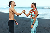 Beach. Woman And Man Greeting Before Workout In Morning. Happy Fitness Couple In Fashion Sportswear. Sport Friends Meeting On Coast. Outdoor Training On Summer Vacation For Active Lifestyle.