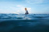 Surf In Ocean. Surfing Man Sitting On White Surfboard. Surfer In Wetsuit In Turquoise Sea. Water Sport For Active Lifestyle.