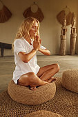 Meditation. Meditating For Relaxation And Mental Balance. Home Yoga Practicing For Healthy Lifestyle. Mature Woman Sitting On Low Seat In Lotus Pose.