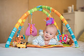 Newborn baby boy lying on a bed and playing on play mat, baby gym