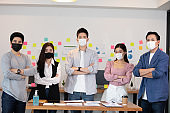 Group of Happy Asian business men leader standing wearing mask smile cross arm confidence with Business team at Co-Working space or modern office Due Covid-19 flu pandemic