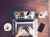Top views woman working with laptop and VDO Call Conference to meeting business team during quarantine coronavirus sitting on wooden table at home,Video conference work from home concept
