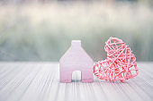 Pink wooden heart design with miniature pink wooden house over blurred background