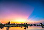 The sun rays on the horizon dramatically through clouds