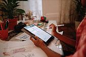 Female designer working at home on a digital tablet