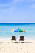 Summer concept background, beach chair and colorful umbrella on the beach with blue sea and clear sky view