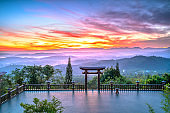 Dawn in front of temple gate with impressive colorful clouds in sky shines under mist valley