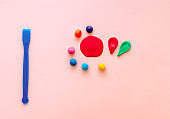 cute flower made of multi-colored plasticine clay on a pink background, multi-colored dough, minimal, children's crafts