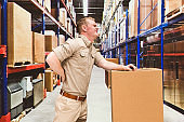 Caucasian male working class bending over at the warehouse wearing button down shirt and holding cardboard box