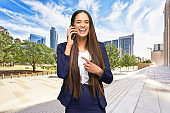 African-american ethnicity young women businesswoman standing who is outdoors wearing businesswear and using mobile phone