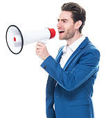 Caucasian young male businessman standing in front of white background wearing businesswear and holding megaphone