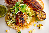 Fish tacos served on homemade corn tortilla with shredded cabbage, grilled corn, queso Fresca, jalapeños served with cilantro, guacamole and spicy salsa verde. Classic Mexican or Tex-Mex street food favorite.