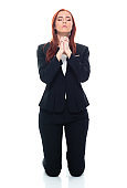 Caucasian female business person kneeling in front of white background wearing businesswear