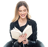 Front view / one person / waist up / portrait of 20-29 years old adult beautiful blond hair / long hair caucasian / generation z female / young women student / university student wearing leather jacket / pants / t-shirt / shirt / sitting on chair