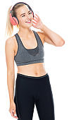 Caucasian teenage girls exercising in front of white background wearing sports bra and using headphones