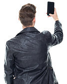 Caucasian boys photography standing in front of white background wearing t-shirt and using mobile phone