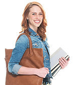 Caucasian female student wearing denim jacket and holding textbook