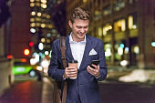 Young male business person standing in front of defocused background wearing satchel - bag and holding coffee cup and using smart phone
