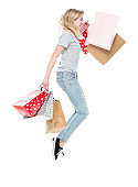 Generation z female shopaholic jumping wearing jeans and holding bag