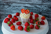 Cupcake in the center with white cream decorated with ripe strawberries on a gray blue background and scattered strawberries