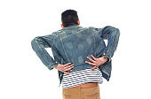 African ethnicity male standing in front of white background wearing denim jacket