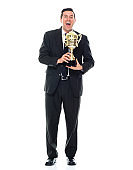 Caucasian young male businessman standing wearing businesswear and holding trophy