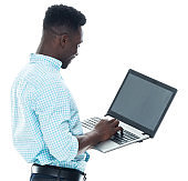African ethnicity young male standing wearing shirt and using computer