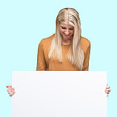 Caucasian young women presenter standing in front of colored background wearing pants and holding banner sign