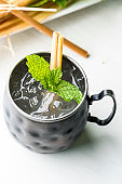 Moscow Mule, classic cocktail made with vodka, ginnger ale served in a copper mug and garnished with mint and lime