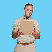 Caucasian young male delivery person standing in front of blue background wearing button down shirt and holding clipboard
