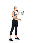 Caucasian female standing in front of white background wearing leggings and holding megaphone