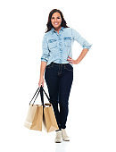 Caucasian female shopaholic in front of white background wearing jeans and holding bag