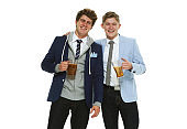 Teenage boys hipster in front of white background wearing sweatshirt and holding ale