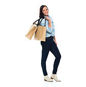 Caucasian mid adult shopaholic in front of white background wearing shirt and holding shopping bag