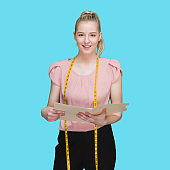 Caucasian female owner standing in front of blue background wearing pants and holding contract and using tape measure