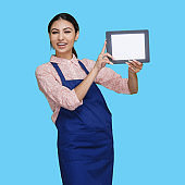 Latin american and hispanic ethnicity young women in front of blue background wearing shirt and using touch screen
