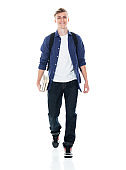 Boys junior high student walking in front of white background wearing backpack and holding book