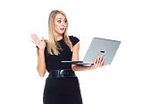 Caucasian young women business person standing in front of white background wearing dress and using computer