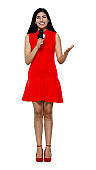 Latin american and hispanic ethnicity young women commentator standing in front of white background wearing dress and holding microphone