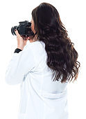 Caucasian young women photographer standing in front of white background wearing lab coat and holding camera