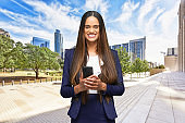 African-american ethnicity young women business person standing who is outdoors wearing businesswear and using smart phone