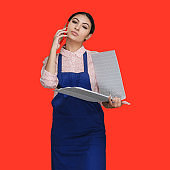 Latin american and hispanic ethnicity young women in front of colored background wearing button down shirt and holding document and using smart phone