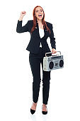 Caucasian female business person exercising in front of white background wearing businesswear and holding tape recorder