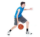 Caucasian boys basketball player in front of white background and holding basketball - ball and using sports ball