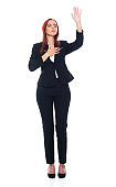 Caucasian female business person standing in front of white background wearing businesswear